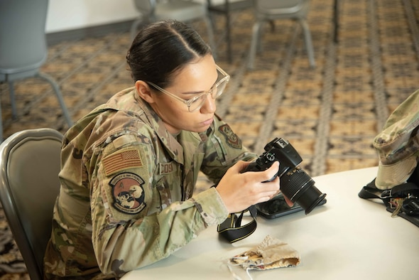 Airman Guinevere Acosta, 436th Operation Support Squadron aircrew flight equipment technician, adjusts her camera's settings at the professional photography workshop during the Fall Wingman Day Series Sept. 16, 2020, at Dover Air Force Base, Delaware. The photography workshop helped Airmen understand and use basic photography skills. (U.S. Air Force photo by Airman Brandan Hollis)