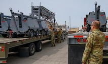 Airmen strap down equipment on flat-bed truck.