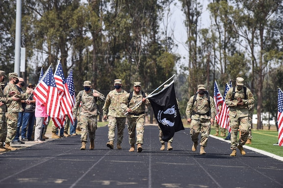 Chief Master Sgt. Daryl Hogan, 30th Space Wing command chief, leads the way, carrying the Prisoner of War and Missing in Action flag, during the first lap around the track at the POW/ MIA Remembrance Ceremony Sept. 17, 2020, at Vandenberg Air Force Base, Calif. The ceremony began with a motorcade, followed by a ceremonial presentation of the POW/ MIA flag and speeches by Vandenberg AFB leadership. After the ceremony, members from across the installation participated in a 24-hour walk or ruck while carrying the POW/ MIA flag, as well as a continuous 24-hour name reading of the past and current POW/MIA members, until the closing ceremony the next day.  (U.S. Air Force photo by Senior Airman Hanah Abercrombie)