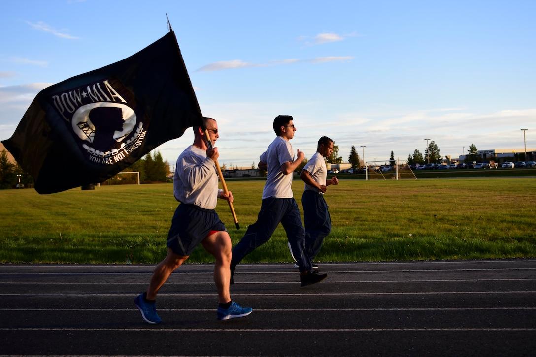 Three airmen run along a track, one with the POW/MIA flag.