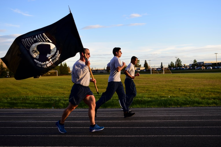 Three airmen run along a track, one with the POW/MIA flag.