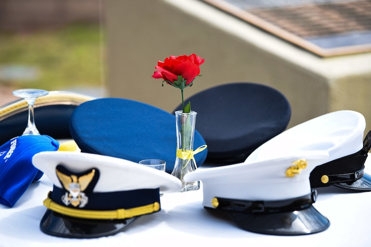 A group of military hats and a rose in a vase sit on a table.