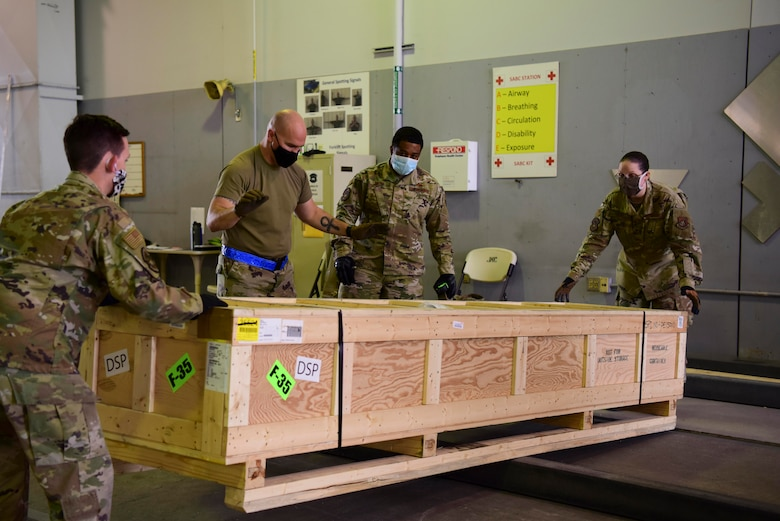U.S. Air Force Airmen assigned to the 354th Logistics Readiness Squadron search for the center of the crate during Arctic Fox 20-2 on Eielson Air Force Base, Alaska, Sept. 15, 2020. The objective of this step is to find the item's center to avoid throwing off the balance of a cargo plane that it is going to be loaded on. (U.S. Air Force photo by Airman 1st Class Jose Miguel T. Tamondong)