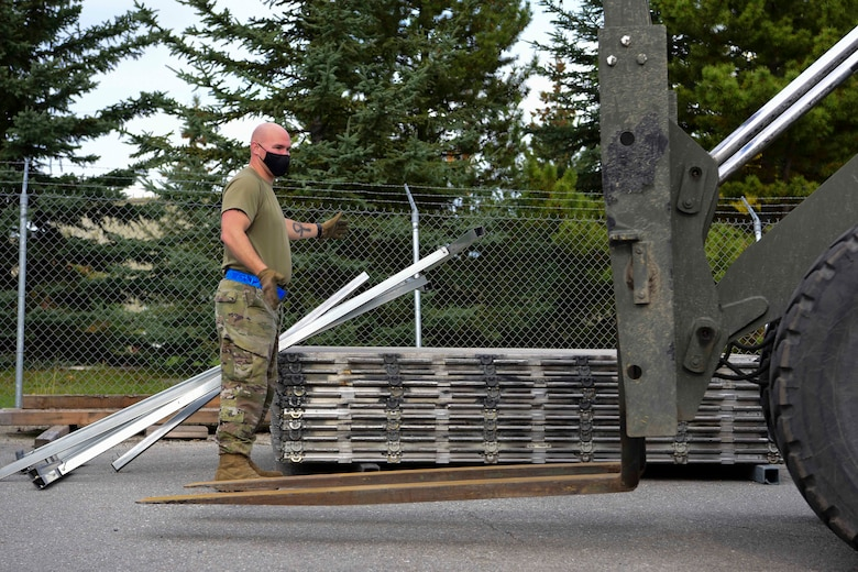 U.S. Air Force Staff Sgt. Jordan Ackley, the 354th Logistics Readiness Squadron noncommissioned officer in charge of the cargo deployment function, guides a forklift during Arctic Fox 20-2 on Eielson Air Force Base, Alaska, Sept. 15, 2020. The objective of the exercise is to test the unit's capabilities to deploy 11 chalks of aircraft cargo over the course of five days. (U.S. Air Force photo by Airman 1st Class Jose Miguel T. Tamondong)