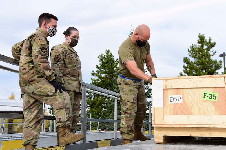U.S. Air Force Airmen assigned to the 354th Logistics Readiness Squadron (LRS) prepare to restrain a crate during Arctic Fox 20-2 on Eielson Air Force Base, Alaska, Sept. 15, 2020. The 354th LRS is responsible for passing assets to deploying. (U.S. Air Force photo by Airman 1st Class Jose Miguel T. Tamondong)