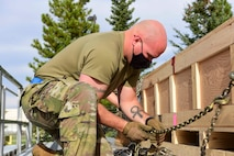 U.S. Air Force Staff Sgt. Jordan Ackley, the 354th Logistics Readiness Squadron noncommissioned officer in charge of the cargo deployment function, uses a chain to restrain a crate during Arctic Fox 20-2 on Eielson Air Force Base, Alaska, Sept. 15, 2020. This process restrains the movement of the pieces in all directions with minimal use of equipment or cargo straps. (U.S. Air Force photo by Airman 1st Class Jose Miguel T. Tamondong)