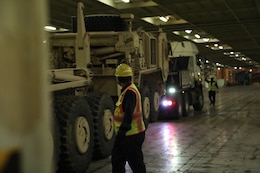 Contractors move pieces of heavy equipment into their spaces at the Port of Shuiaba, Kuwait, September 11, 2020. The 1184th Deployment and Distribution Support Battalion, from Mobile, AL is responsible for the movement of nearly 400 pieces from several different units on this shipment. (U.S. Army Reserve Photo By Sgt. Vontrae Hampton)