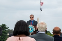 The deputy secretary speaks at at a podium to an audience outdoors.