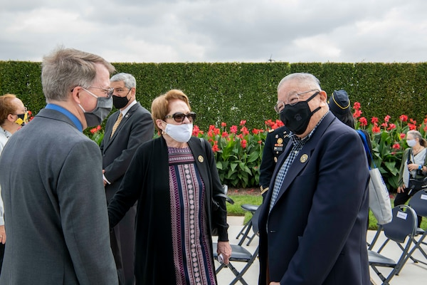 The deputy secretary talks with two attendees at an outdoor ceremony.