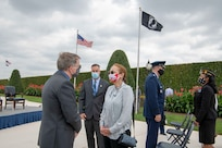 The deputy secretary talks with an attendees at an outdoor ceremony.