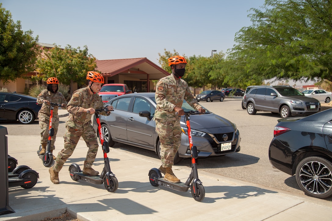 Team Edwards personnel demonstrate the new Spin scooters near the Airmen dormitories at Edwards Air Force Base, California, during the projects launch Sept. 2. (Air Force photo by Ethan Wagner)