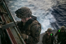 PHILIPPINE SEA (Sept. 9, 2020) A Marine with the Amphibious Reconnaissance Platoon, 31st Marine Expeditionary Unit (MEU), climbs down a caving ladder to board a rigid-hull inflatable boat from the amphibious assault ship USS America (LHA 6) to conduct a reconnaissance and surveillance training mission in preparation for a boat raid.