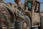 U.S. Army Spc. Tou Vang acts as a guide for U.S. Army Sgt. Kyle Karolus as he moves a conex container at Camp Taji, Iraq July 18, 2020. As members of the Alpha Distro processing center with Alpha Company, 834th Aviation Support Battalion, these Soldiers play a key role in shipping all U.S. owned property before the base transfers from Coalition to Iraqi Security Forces control. (U.S. Army photo by Sgt. Sydney Mariette)