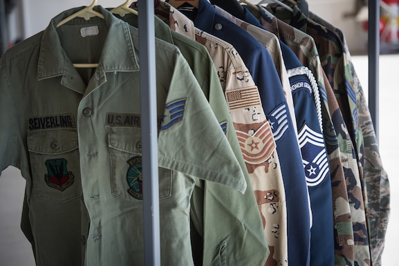 An array of U.S. Air Force uniforms worn by Chief Master Sgt. Scotty Seiverling are on display during his retirement ceremony.