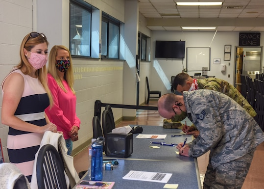Jolene Richardson (left) and A.J. Byerly (right), both directors of psychological health for the 193rd Special Operations Wing, encourage Airmen to write supportive notes during a suicide prevention month activity at the wing dining facility Sept. 19, 2020. The handwritten notes were placed on the wall to demonstrate building a wall of support for fellow Airmen. (Air National Guard photo by Staff Sgt. Rachel Loftis/Released)