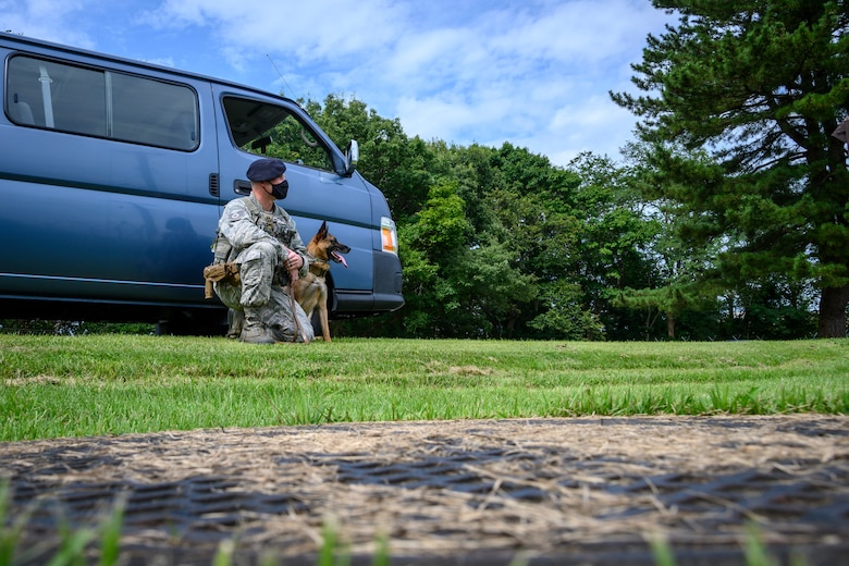U.S. Air Force Staff Sgt. Anthony Rescheka, a 35th Security Forces Squadron military working dog handler, sits with his MWD, Bella, before a demonstration at Misawa Air Base, Japan, Sept. 17, 2020. Working dog handlers with the 35th Security Forces Squadron's K-9 unit display the skills of their dogs during a demonstration for Chief Master Sgt. Rick Winegardner Jr, the U.S. Forces Japan command chief. The dogs train on how to detect explosives and narcotics as well as perform controlled aggression tactics when detaining suspects. (U.S. Air Force photo by Airman 1st Class China M. Shock)