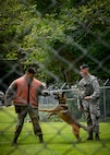 U.S. Air Force Staff Sgt. Amanda Puryear, a 35th Security Forces Squadron military working dog handler, instructs Chief Master Sgt. Rick Winegardner Jr., the U.S. Forces Japan command chief, before a demonstration at Misawa Air Base, Japan, Sept. 17, 2020. Working dog handlers with the 35th Security Forces Squadron's K-9 unit display the skills of their dogs during a demonstration for Chief Master Sgt. Rick Winegardner Jr, the U.S. Forces Japan command chief. The dogs train on how to detect explosives and narcotics as well as perform controlled aggression tactics when detaining suspects. (U.S. Air Force photo by Airman 1st Class China M. Shock)