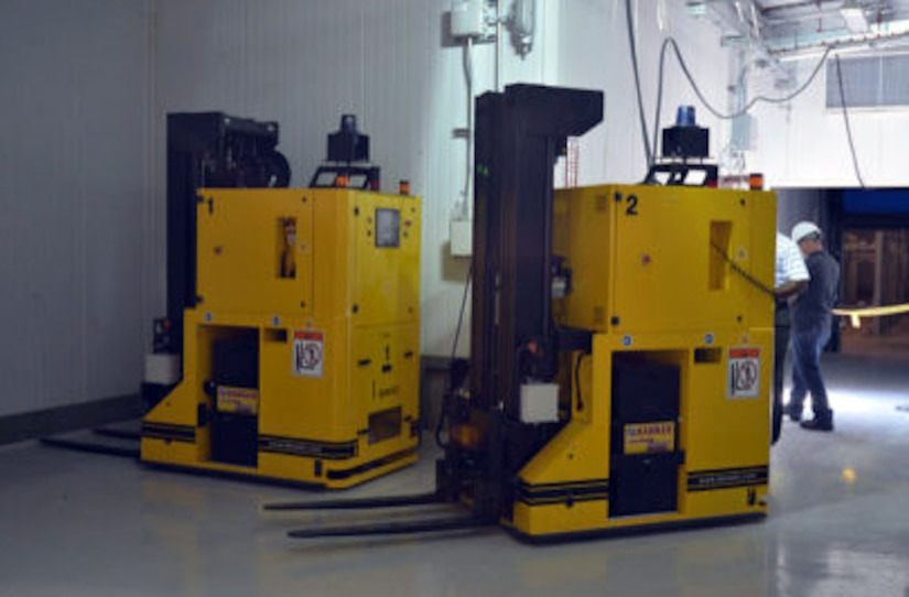 Two large yellow machines sit on the floor.