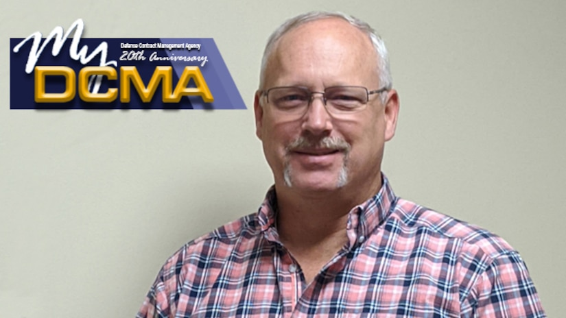 Man wearing striped shirt stands against a wall with the My DCMA logo placed in the upper left portion of the photo