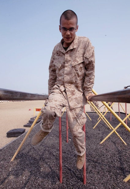 A recruit with Hotel Company, 2nd Recruit Training Battalion, climbs over an obstacle during the Confidence Course at Marine Corps Recruit Depot, San Diego, Sept. 14, 2020.