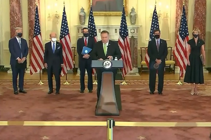 A line of people stand on a podium.