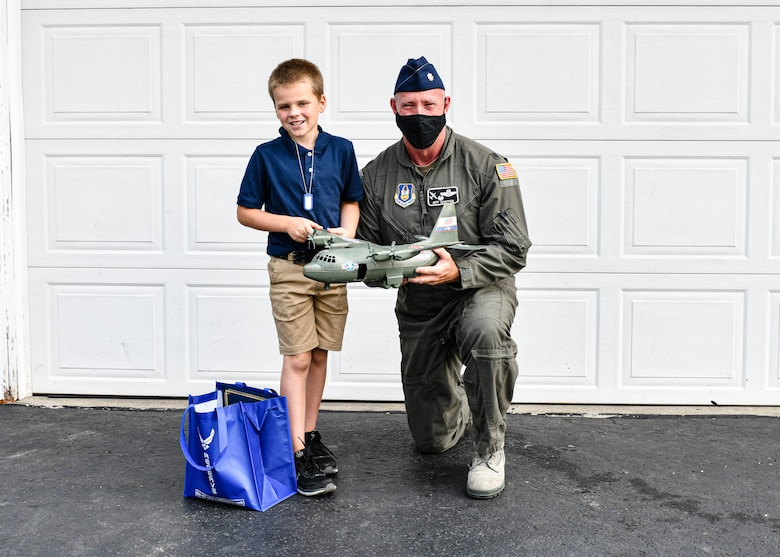 910th Operations Group Commander Lt. Col. Jeff Shaffer delivered Air Force Reserve swag to the McCloskey family in recognition of their son's love for C-130 aircraft and support of the unit.