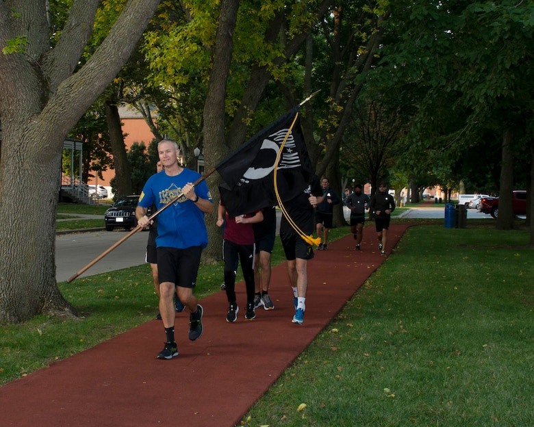 Command Chief  Brian Thomas running while carrying the POW/MIA flag, behind him a group of Airmen in civilian clothing