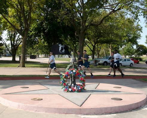 in the front of photograph is the Prisoner of War/Missing in Action Memorial with a large wreath leaning against it. In the background an Airman running while carrying the POW/MIA flag running with four other Airmen running behind him