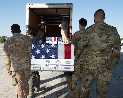 in the foreground, six Airmen carry a U.S. flag draped transfer case to a transportation truck in the background, two civilians stand inside with hands over there hearts, inside the truck are two previously loaded transfer cases