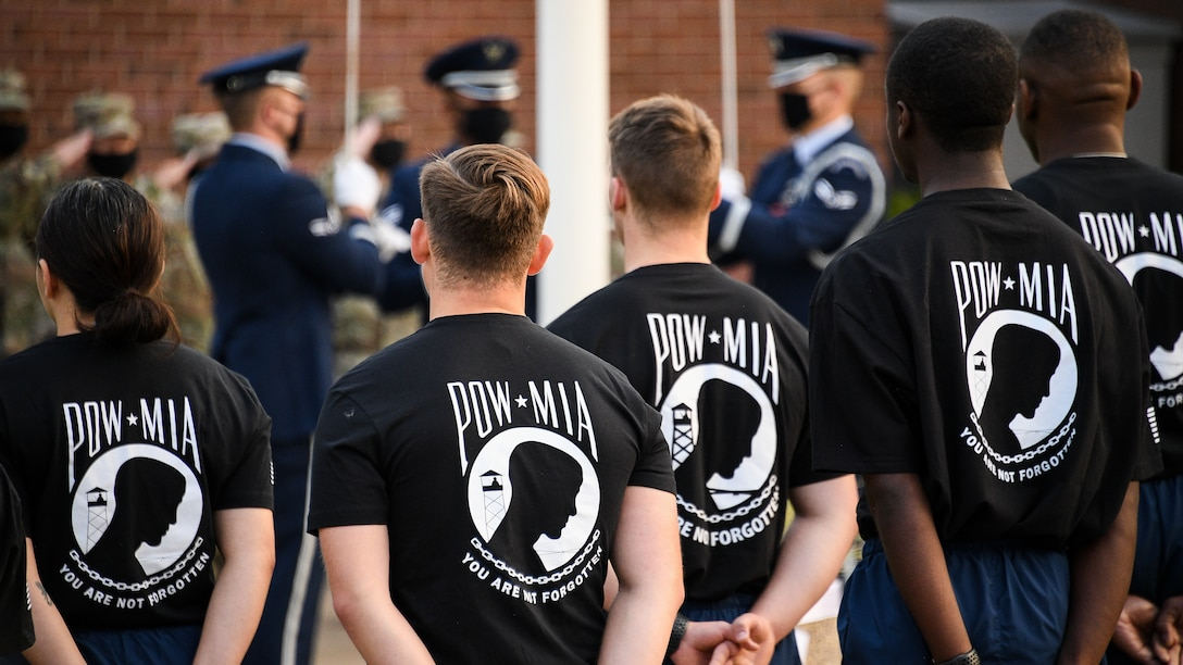 Airmen participating in a 24-hour POW/MIA vigil run stand in formation for a flag raising and opening ceremony.