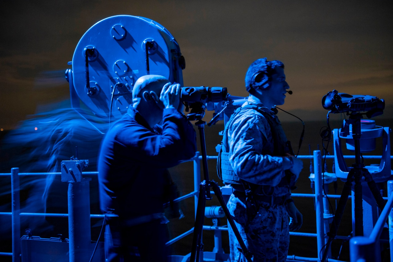 Sailors stand watch on ship at night.