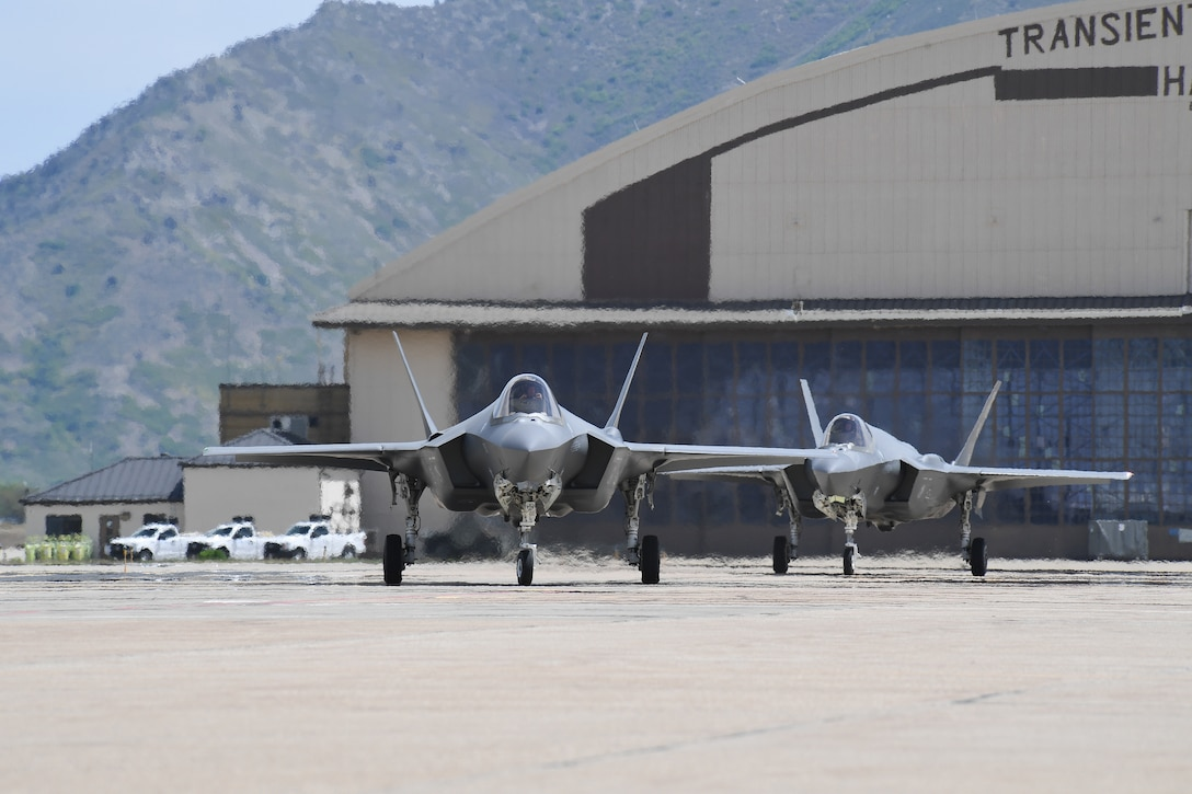 Jets sit in front of a hangar.