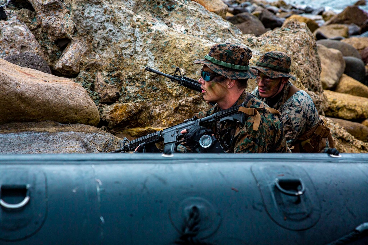 Two Marines wearing camouflage paint carry rifles while positioned against rocks.