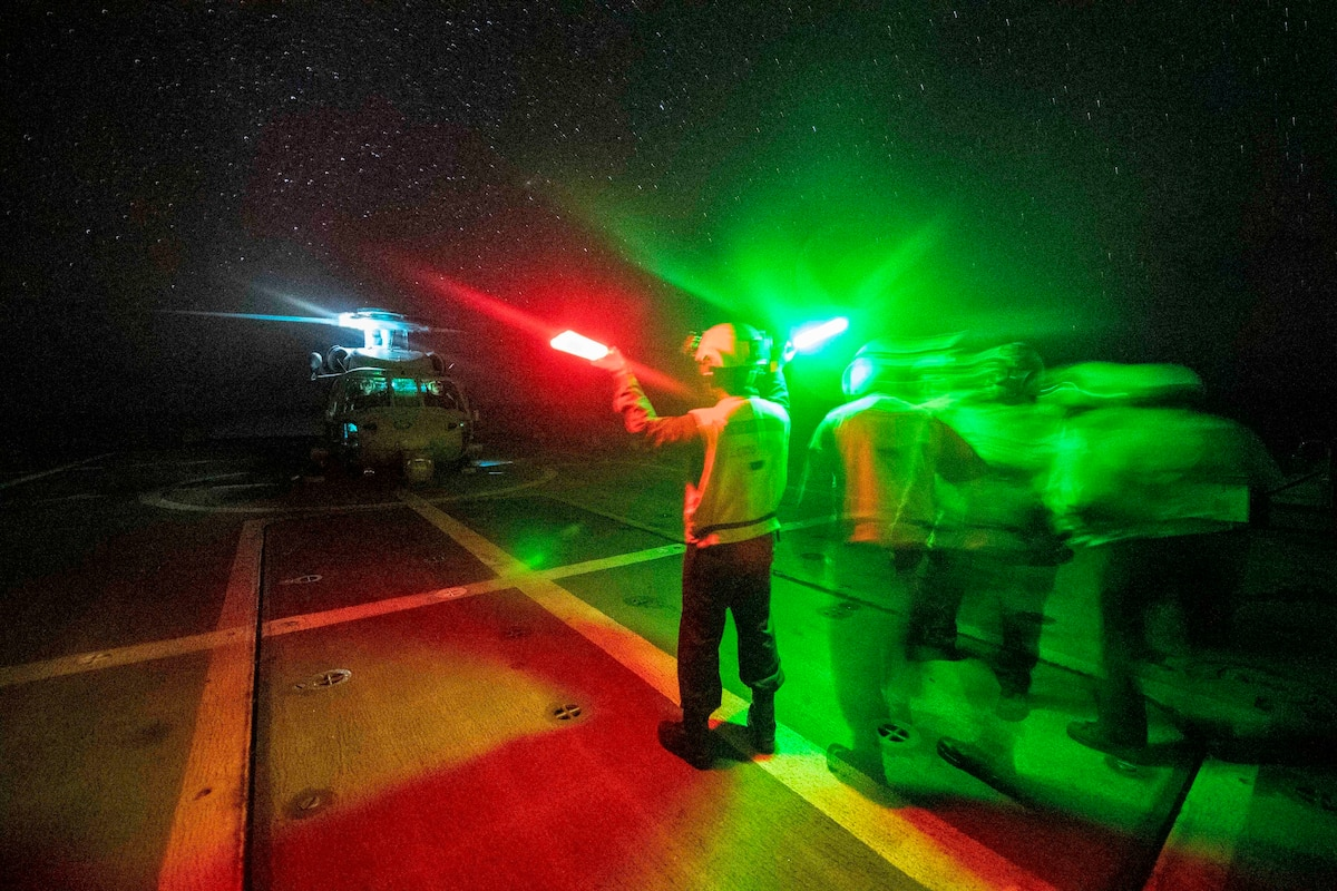 Sailors bathed in red and green colors signal a helicopter onto the deck of a ship.