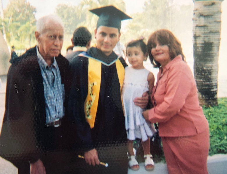 A young Master Sgt. Heriberto Mercado Rodriguez, 27th Special Operations Logistics Readiness Squadron C-130 aircraft parts storage section chief, takes a photo with his family after graduating from the University of Puerto Rico at San Juan, Puerto Rico. Mercado graduated college while running a business and starting a family. (Courtesy Photo)
