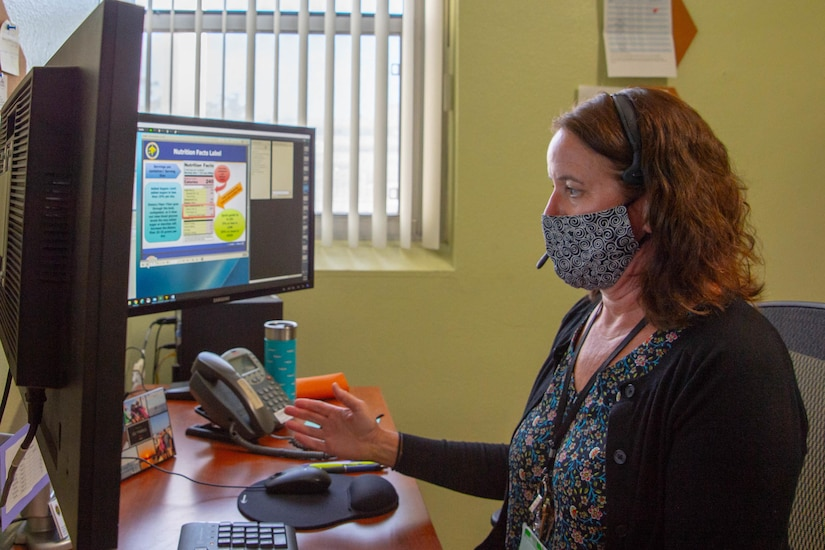 A woman wearing a mask uses computer.