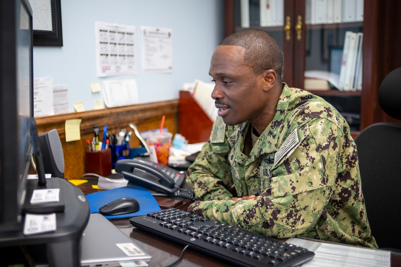 A man in a uniform works at a computer.