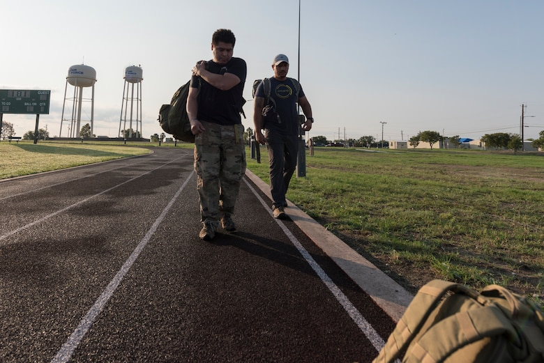 Participants adjust their gear before starting the ruck competition that was held on base in celebration of the Air Force's 73rd birthday on Sept. 18, 2020, at Laughlin Air Force Base, Texas. The wing hosted a ruck competition following a dissimilar formation flyover and playing of the Air Force song. (U.S Air Force photo by Senior Airman Anne McCready)