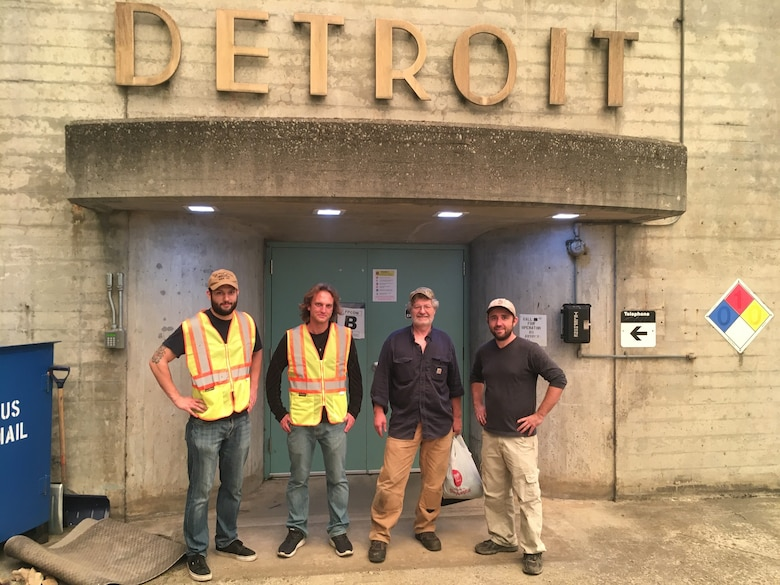 Four men stand in front of doors, with a sign above them that reads Detroit.