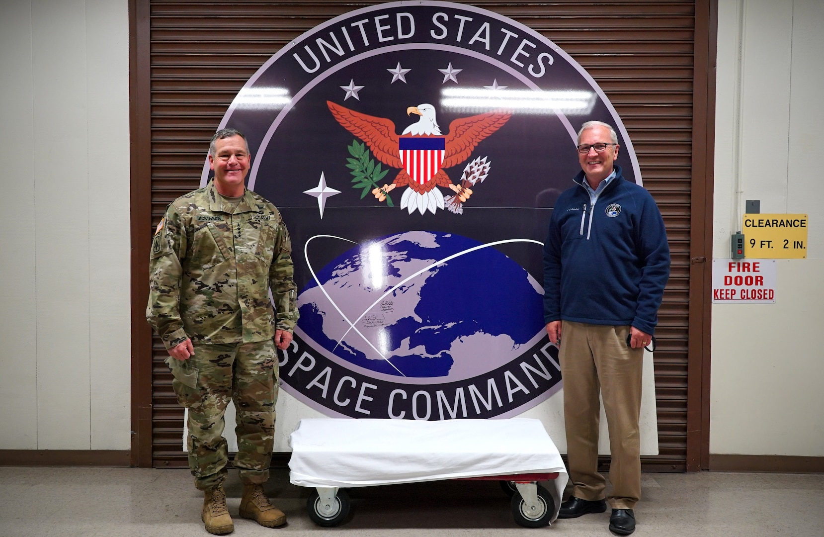 A circular U.S. Space Command seal stands nearly seven feet tall and wide between two men who smile for a photo beside it.