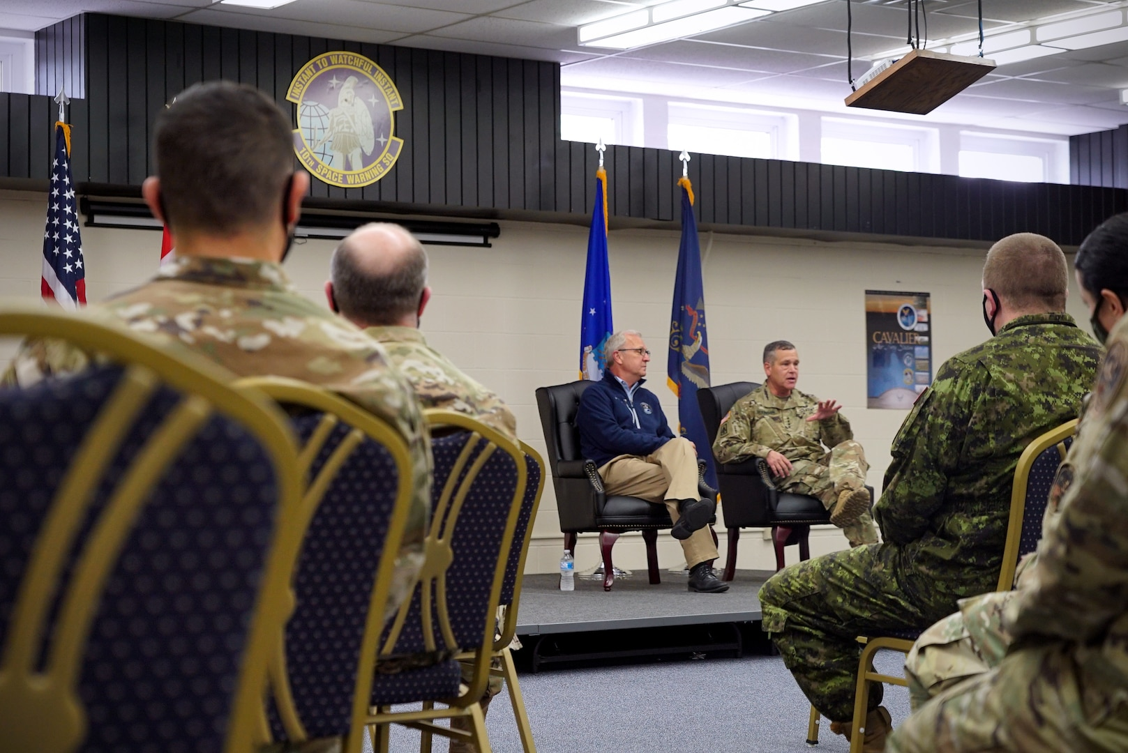 An audience of military members sit with their backs to the foreground of a photo that focuses on two men sitting on-stage in dark blue chairs.