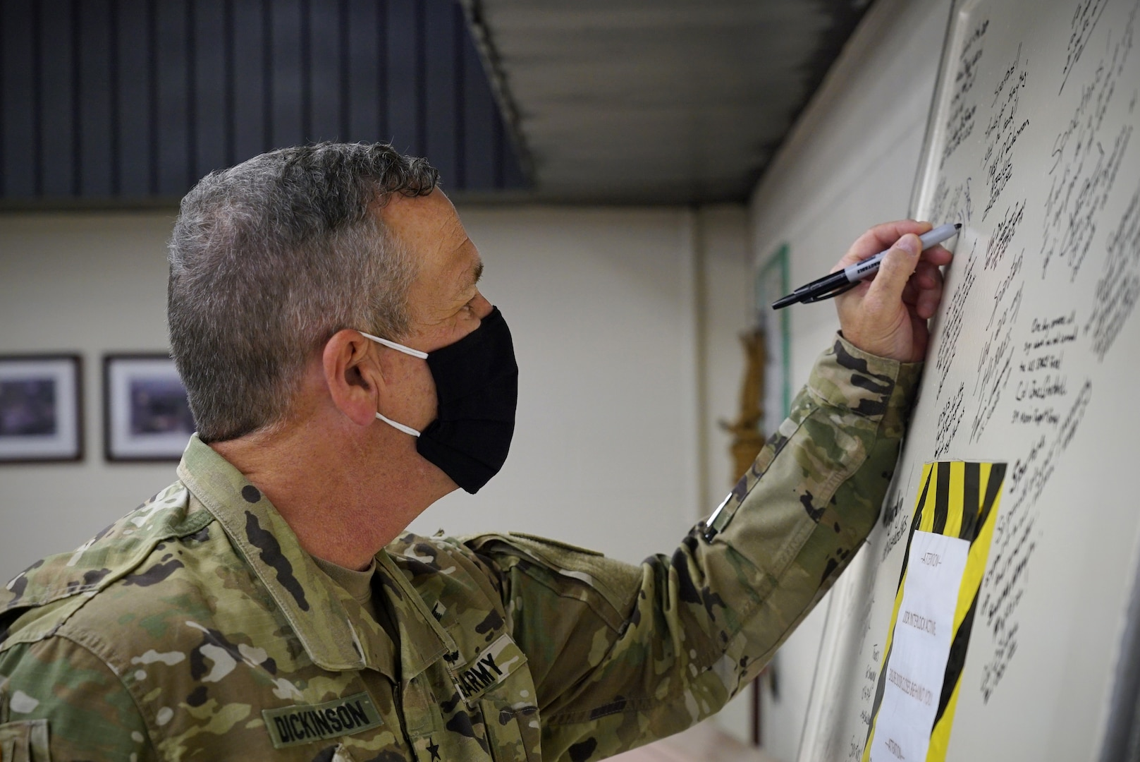 A man in military uniform uses his left hand to leave his signature in permanent marker on a door leaning up against the wall in front of him.