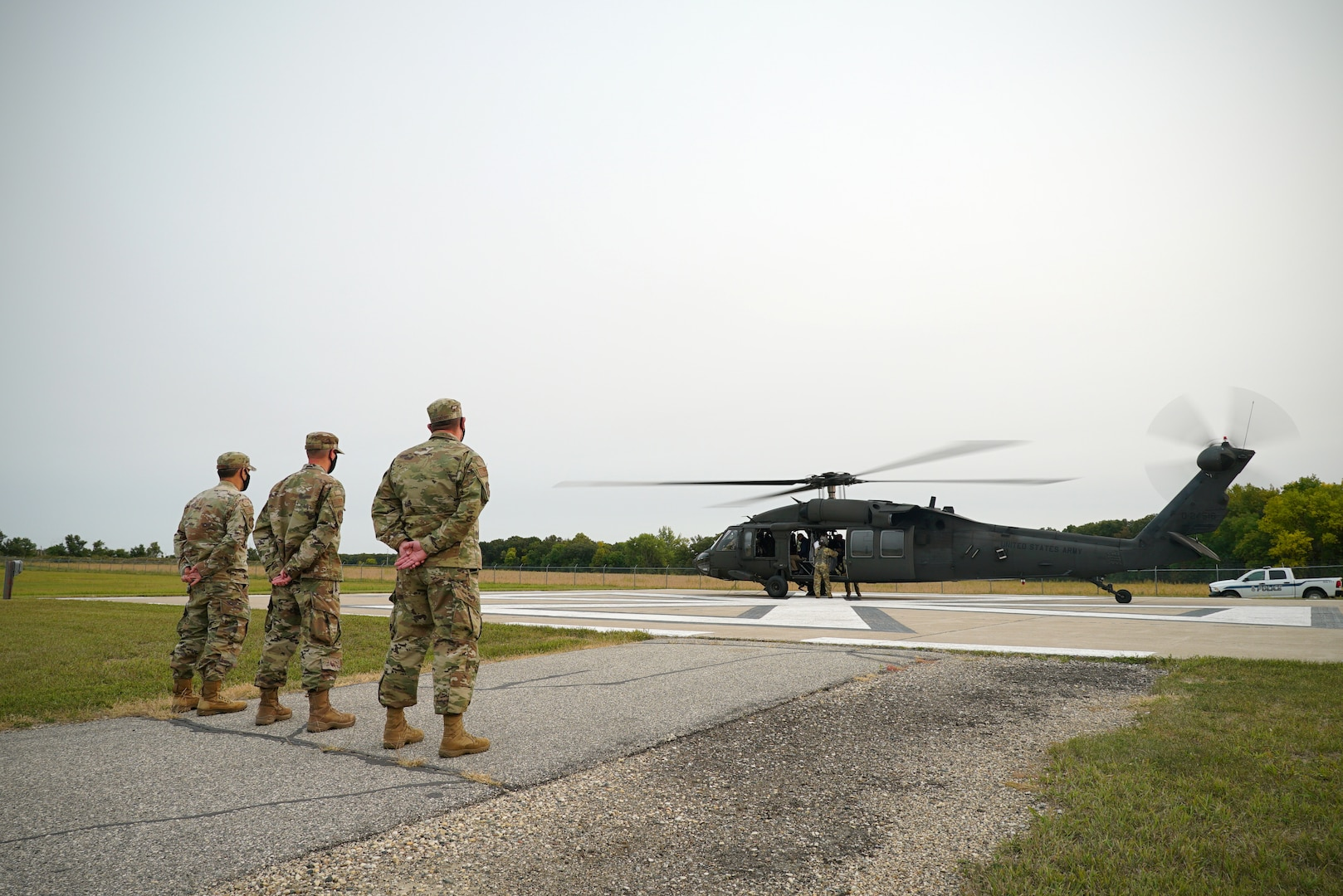 Three men in military uniform stand at parade rest on the left-hand side of the screen, awaiting the departure of a UH-60 Black Hawk seen on the right-hand of the screen.