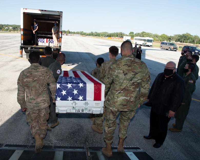 in foreground six Airmen walking off airplane ramp carrying a U.S. flag draped transfer case, walking to a transportation vehicle in the background