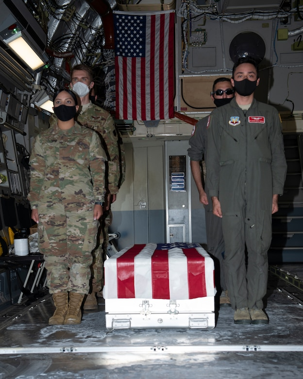 Airmen inside cargo area of airplane, standing at attention next to a U.S. flag draped transfer case