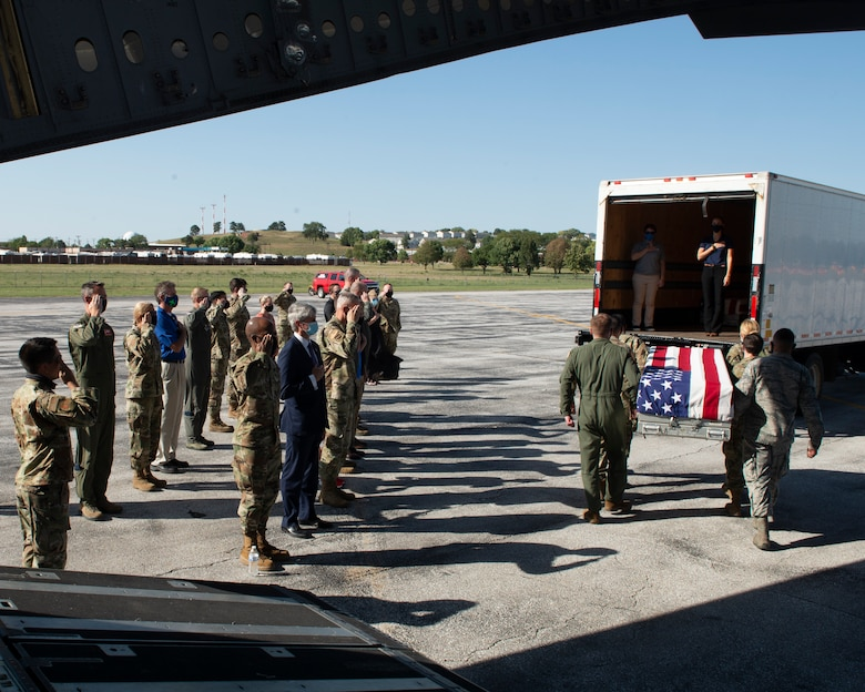 military members and civilians saluting as six Airmen carry a U.S. draped transfer case to a transportation vehicle