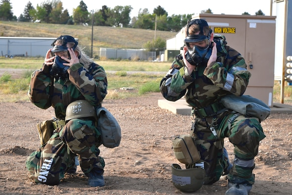 Senior Airman Ashley Epperson (left), 75th Communications and Information Directorate, and Senior Airman Colten Jones Riquelme, 75th Aerospace Medicine Squadron, don protective gear