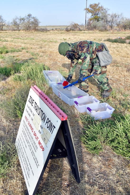 Airman 1st Class Jordan Vassallo, 75th Air Base Wing Communications and Information Directorate, simulates removing contamination from a weapon.