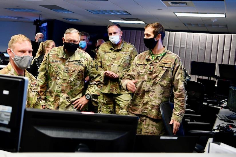 Four men in uniform observe a computer screen.
