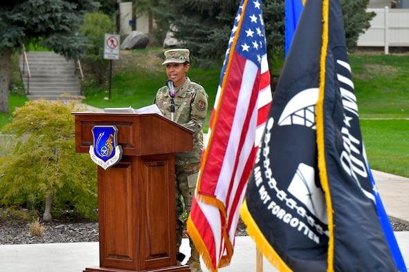 Presiding officer Col. Jenise Carroll, 75th Air Base Wing commander, addresses attendees from behind a podium next to the American and POW/MIA flags.